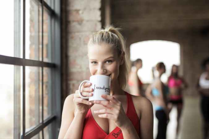 woman in red scoop neck tank top holding white mug